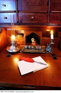 Antique writing desk with red feather quill pen and oil lamp